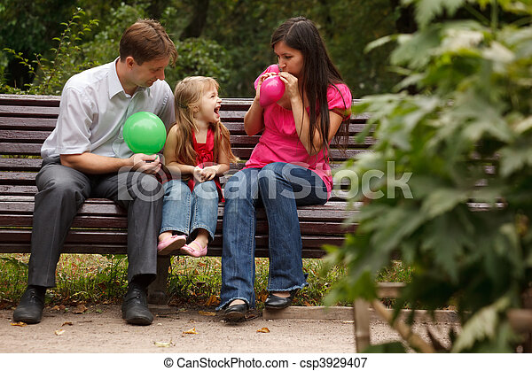 Parents together with daughter on bench in park in afternoon. Parents inflate multi-coloured balloons. - csp3929407