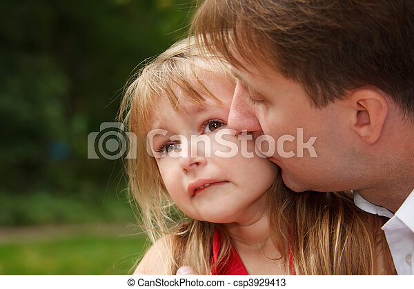 Sad little girl cries in park. Father calms her kissing on cheek.  Close up. - csp3929413