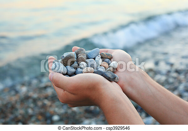 Handful of stones in hands, Against stones and sea - csp3929546
