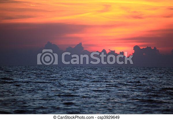 Orange drama sunset over dark gloomy sea - csp3929649