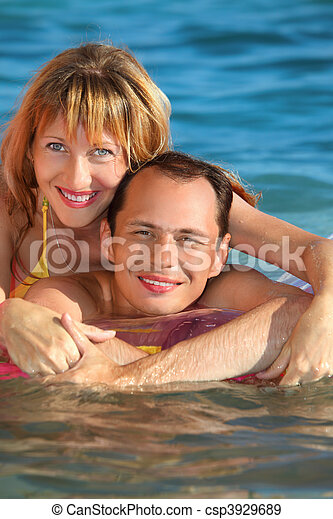 young man and nice women lying on an inflatable mattress in pool, woman lying astride man - csp3929689