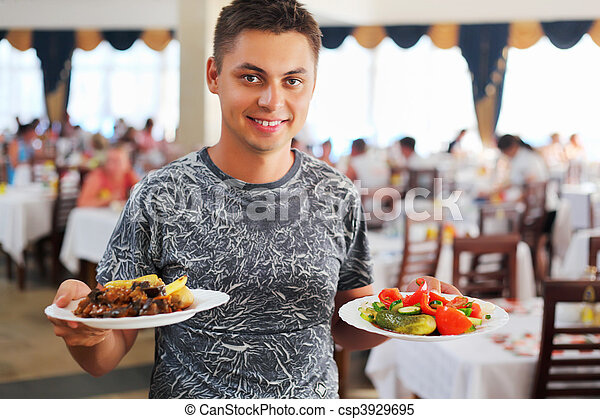 young smiling man with two dishes in hands at restaurant - csp3929695