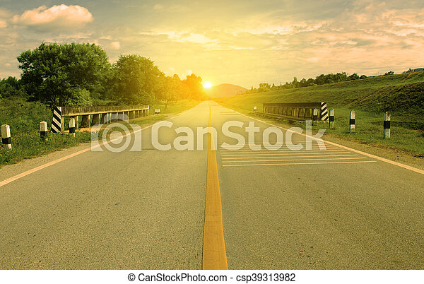 Picturesque landscape scene and sunrise above road.