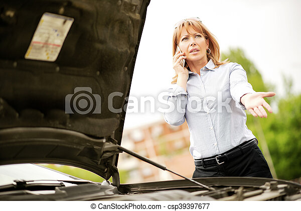 Woman with car trouble in the middle of the street, after car breakdown. She is on the phone, calling for assistance.
