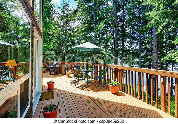 Balcony house exterior with patio area and opened green umbrella. Also wooden railings and flowers pots. Northwest, USA