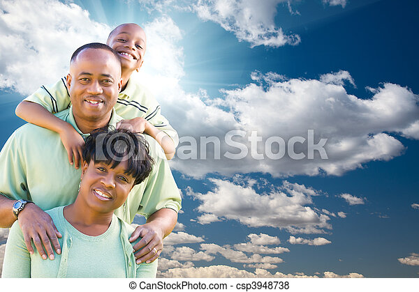 Happy African American Family Over Blue Sky and Clouds - csp3948738