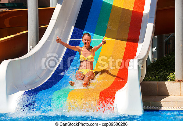 Girl on water slide at water park show thumb up in two hand . Water slides with flowing water in water park.
