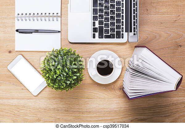 Closeup of wooden office desktop with blank white phone, plant, coffee cup, hardcover book, spiral notepad with pen and laptop. Mock up