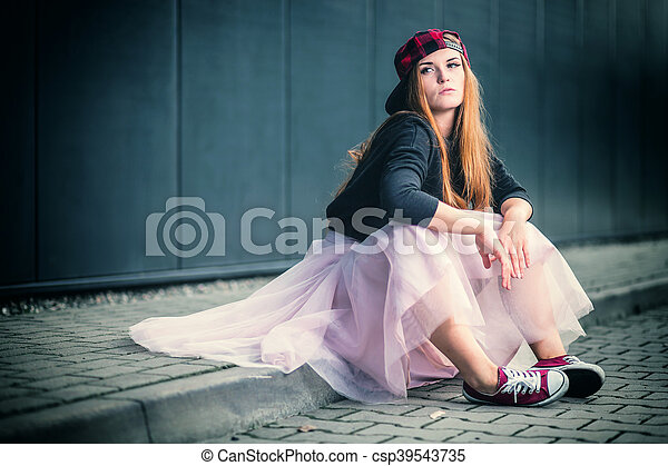 Trendy beautiful long haired girl posing on street, hip hop fashion