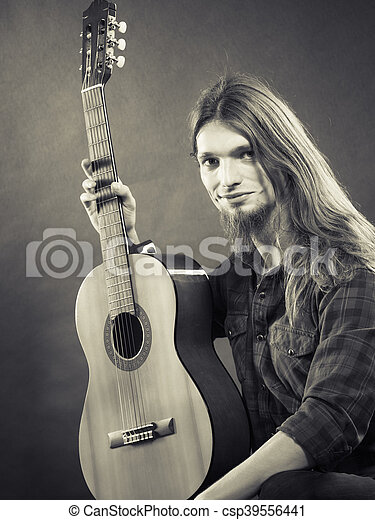 Music, hobby concept. Black and white picture with artist. Young man is holding his beloved guitar.