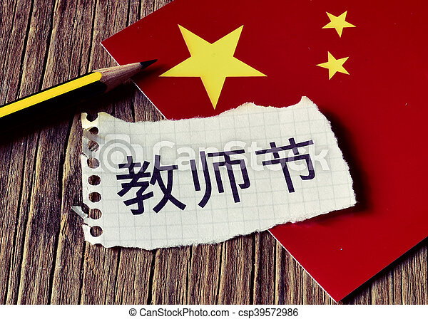 closeup of a peace of paper with the text Teachers Day written in Chinese, a pencil and the flag of China, placed on a rustic wooden surface