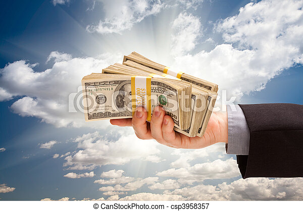 Male Hand Holding Stack of Cash Over Clouds and Sky - csp3958357