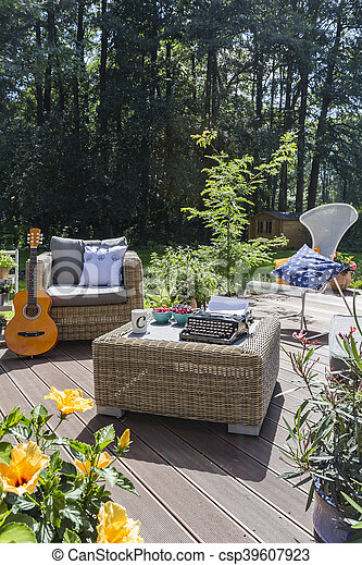 New style patio with rattan sofa, chair and armchair, trees in the background