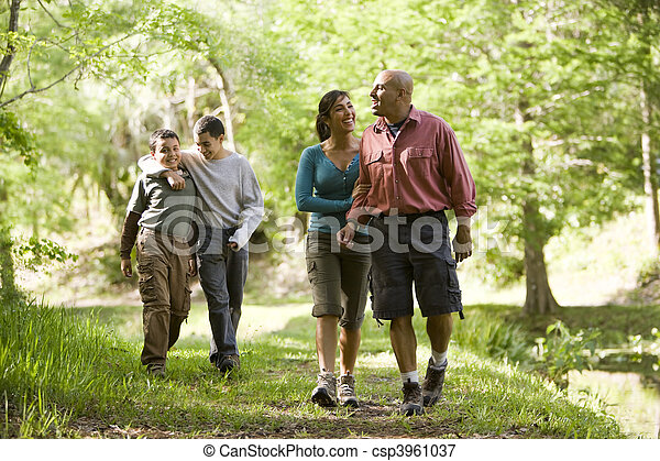 Hispanic family walking along trail in park - csp3961037