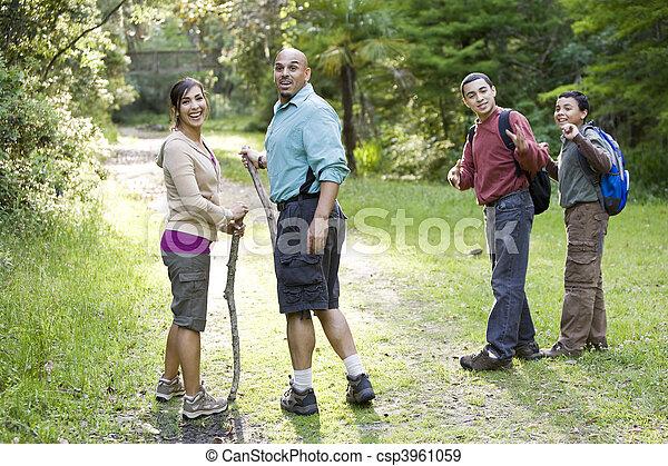 Hispanic family hiking in woods on trail - csp3961059