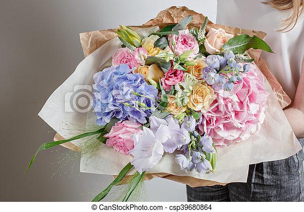 Florist at work. Make Serenity hydrangea rich bouquet. flowers in their hands.