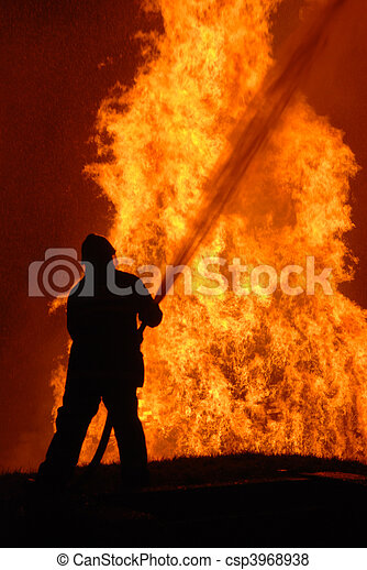 lone fireman battling against raging fire, NOTE: shallow focus on material burning in fire, top left corner particles from water spray, not camera noise - csp3968938