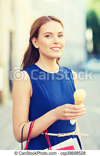 sale, consumerism, summer and people concept - happy young woman with shopping bags and ice cream on city street