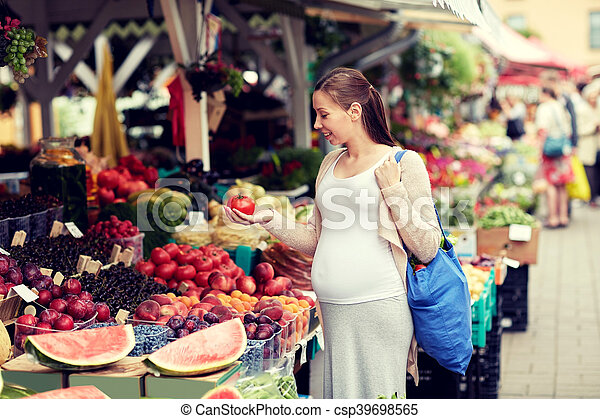 sale, shopping, food, pregnancy and people concept - happy pregnant woman with bag holding tomato at street market