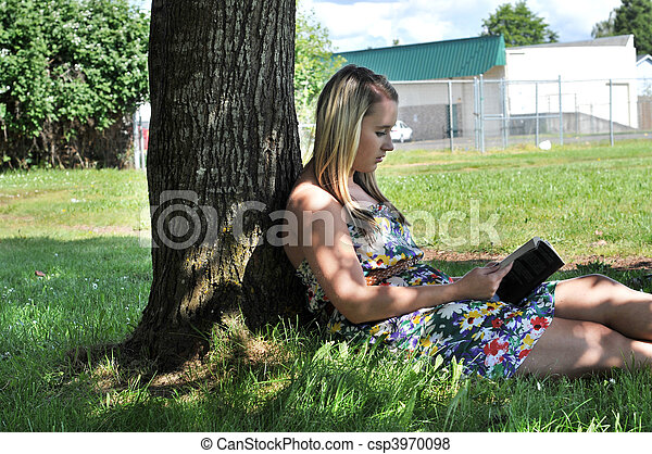 Girl reading book under tree in shade - csp3970098