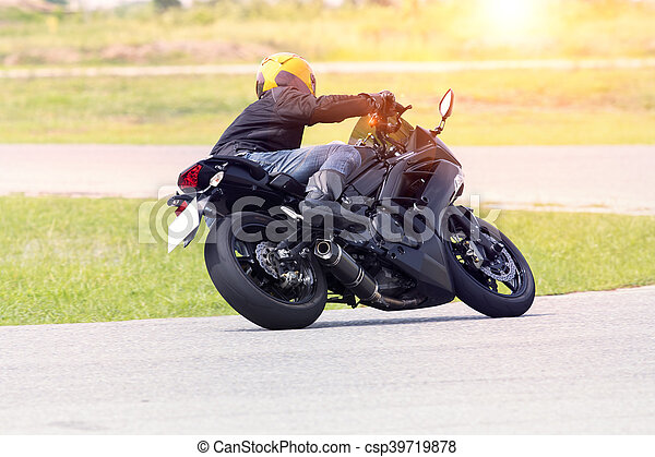 young man riding motorcycle in asphalt road curve wearing full safety suit