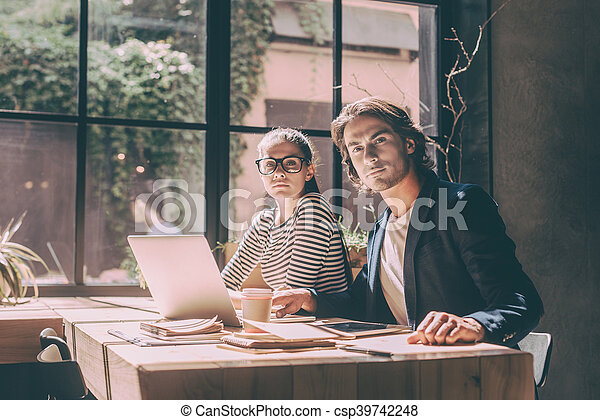 Confident and successful. Confident young man and woman looking at camera while both sitting at the wooden desk in creative office