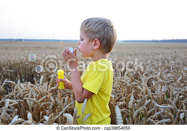 little boy among wheat ears