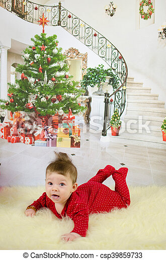 baby girl enjoying her first Christmas with lots of gifts under Christmas tree