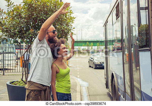 Young couple waving goodbye to their friends on the bus - csp39893674