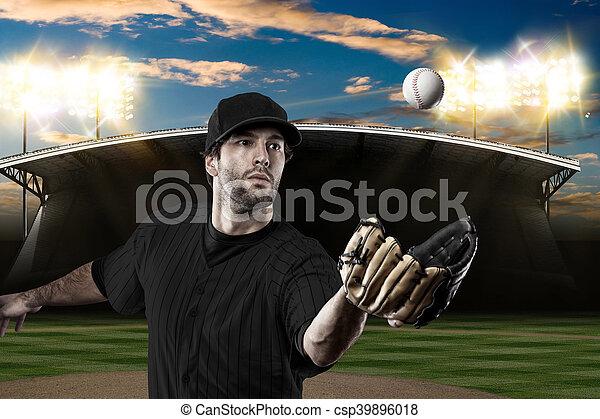 Baseball Player with a black uniform on baseball Stadium.