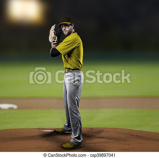 Pitcher Baseball Player with a yellow uniform on baseball Stadium.