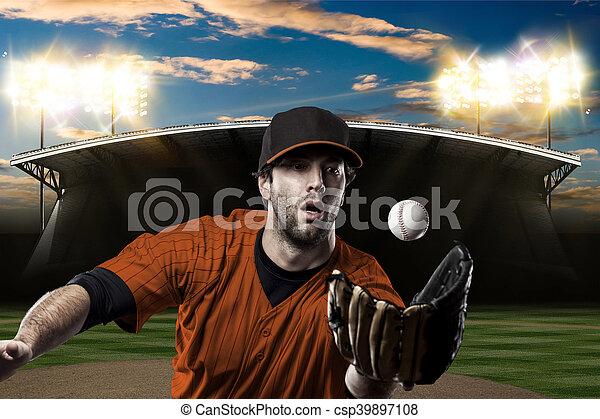 Baseball Player with a orange uniform on baseball Stadium.