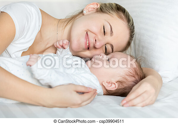 Closeup portrait of beautiful smiling woman lying with her cute baby on pillow at bed