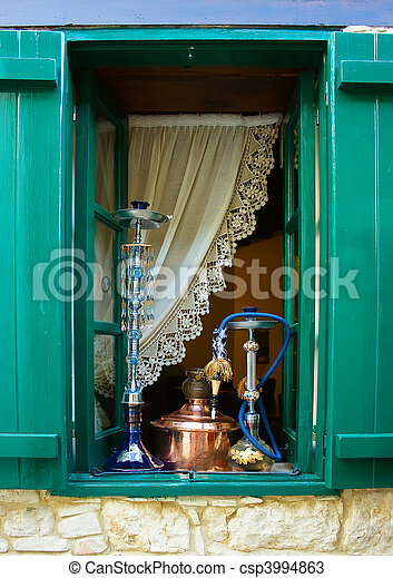 Window with wooden shutters and hookahs on inside sill  - csp3994863