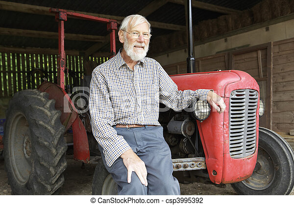 Organic Farmer Sitting Next To Old Fashioned Tractor - csp3995392