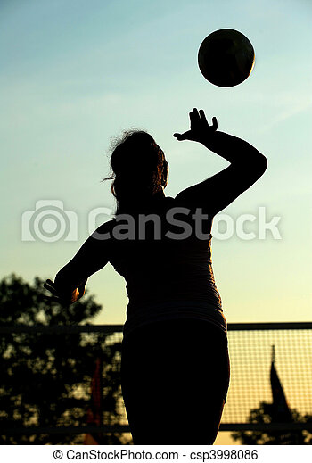 A female beach volleyball player serves during a competition in the late afternoon light. - csp3998086
