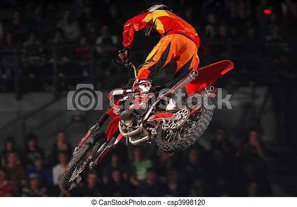 A freestyle moto-x rider goes through a trick during an indoor competition. - csp3998120