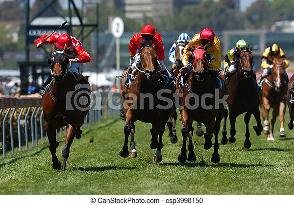 Horses come running toward the camera during a horse race on the grass track. - csp3998150