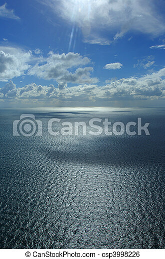 An aerial photograph from a helicopter over a body of water (ocean/sea) with beautiful clouds and sky - csp3998226