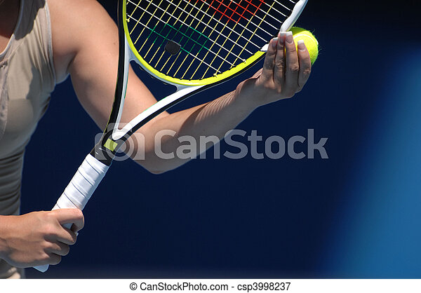 A woman with beautiful hands is holding a tennis ball and raquet preparing for her serve.