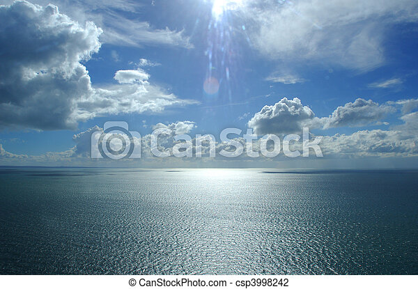 An aerial photograph from a helicopter over a body of water (ocean/sea) with beautiful clouds and sky - csp3998242