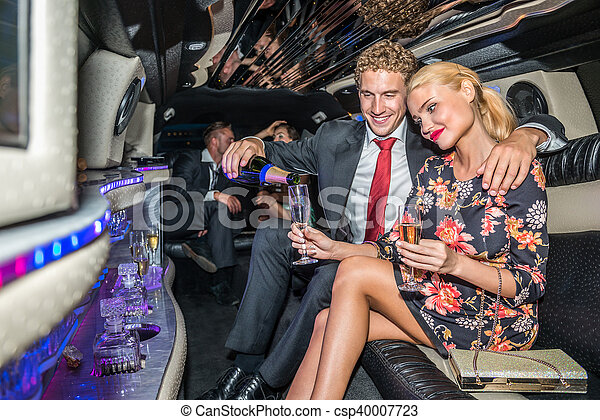 Loving young man serving champagne for girlfriend in limousine - csp40007723
