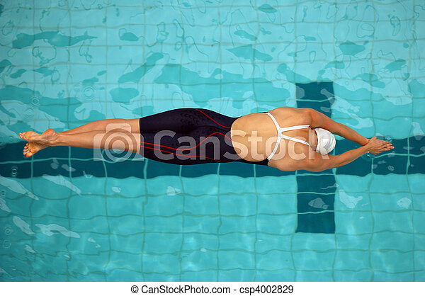 An aerial view of a female swimmer just off the starting blocks - csp4002829