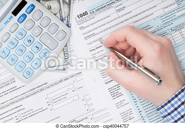 Businessman filling out USA Tax 1040 Form with calculator neat it