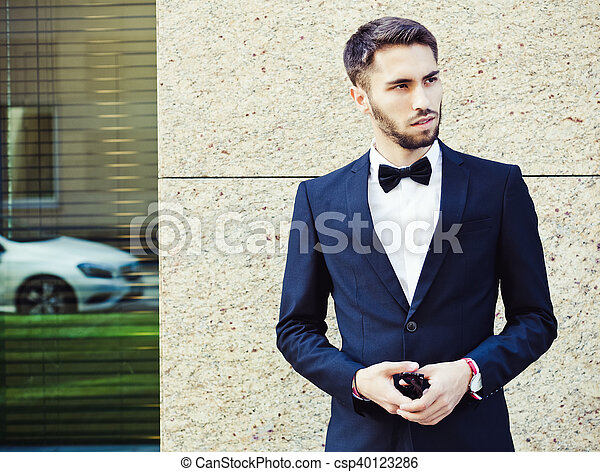 Portrait. Young businessman in a suit and bow tie posing on background of office building. Market. Course. Success. Failure. Shares. Bonds. Oil. Close up. Wall Street Exchange