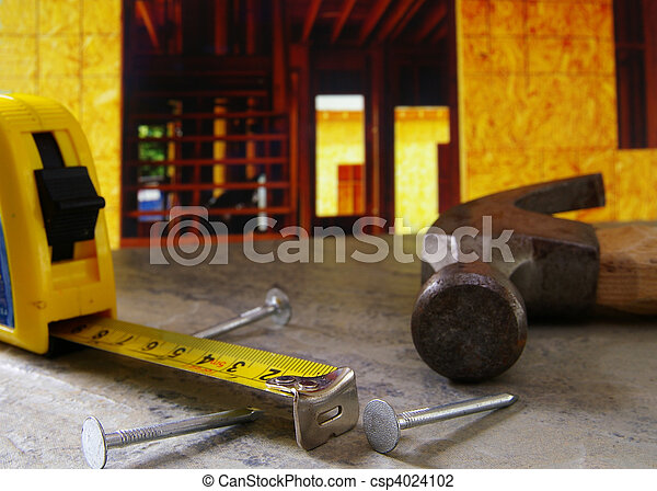 Hammer, nails, and tape measure with new home construction in background - csp4024102