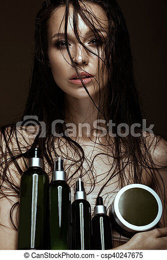 Beautiful girl with a bright make-up and wet hair and skin with bottle of cosmetic products in the hands. Beauty face. Picture taken in the studio on a black background.