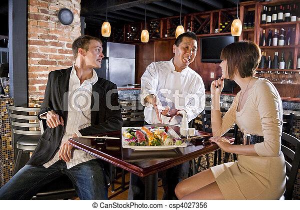 Japanese sushi restaurant, chef serving customers - csp4027356