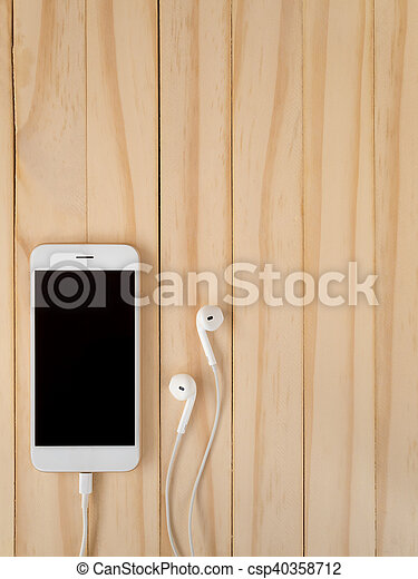 Front view image of new smartphone connecting with charging cable and earbuds on wooden background with copy space.