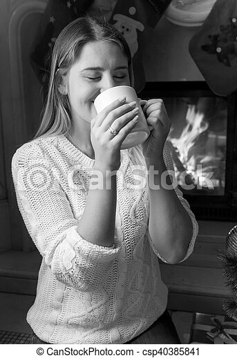 Black and white portrait of beautiful woman drinking tea at the fireplace - csp40385841